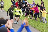 Man helping injured runner finish charity run in park - CAIF20324