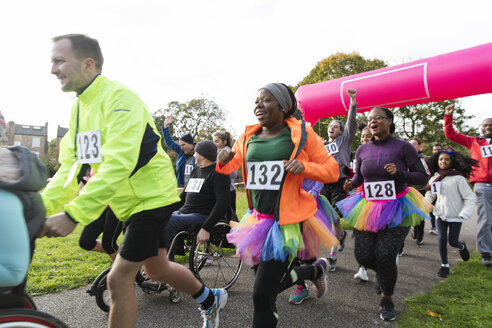 Enthusiastic runners running at charity run in park - CAIF20327