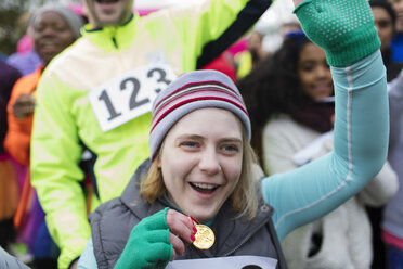 Enthusiastic woman with medal cheering at charity race - CAIF20330