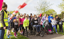 Crowd of runners and people in wheelchairs waiting at charity race starting line - CAIF20333
