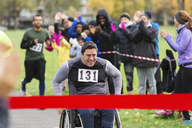 Determined man in wheelchair nearing charity race finish line in park - CAIF20336