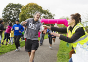 Volunteer giving water to runner at charity run in park - CAIF20339
