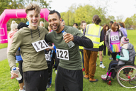 Portrait enthusiastic male runner friends with water hugging at charity run finish line in park - CAIF20342