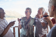 Happy active senior friends drinking wine - CAIF20378