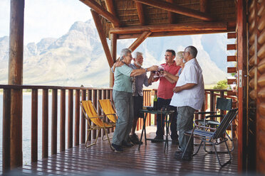 Active senior friends toasting wine glasses on cabin balcony - CAIF20393