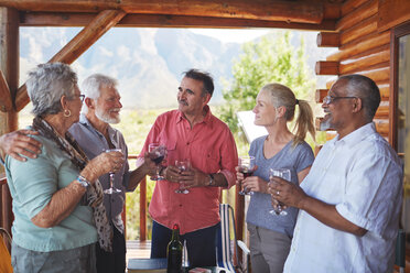 Active senior friends drinking wine on cabin balcony - CAIF20396