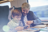 Father and son using smart phone on passenger train - CAIF20399