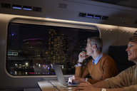 Businessman working at laptop on passenger train at night, looking out window at passing city - CAIF20402