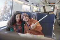 Happy young couple taking selfie with selfie stick on passenger train - CAIF20405