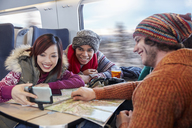 Young friends with map taking selfie with selfie stick on passenger train - CAIF20411