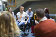 Audience smiling, listening to female speaker with microphone in wheelchair - CAIF20441