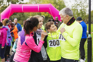 Happy family with medals finishing charity run, celebrating - CAIF20465