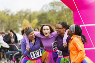 Happy female runners hugging at charity run finish line - CAIF20468