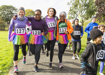 Smiling female runners in tutus walking at charity run in park - CAIF20471