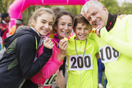 Portrait smiling, confident family runners showing medals at charity run - CAIF20480
