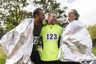 Happy male marathon runners wrapping in thermal blanket - CAIF20483