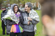 Happy couple runners wrapped in thermal blanket at charity run in park - CAIF20495
