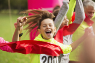 Enthusiastic boy runner crossing charity run finish line - CAIF20498