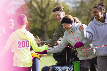 Spectators high-fiving runner at charity run in park - CAIF20501