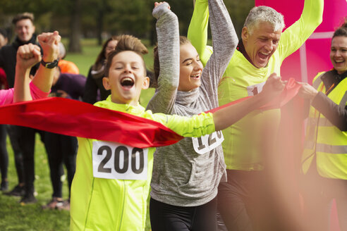 Enthusiastic boy runner crossing charity run finish line with family - CAIF20510