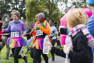 Female runners in tutus running at charity race in park - CAIF20513