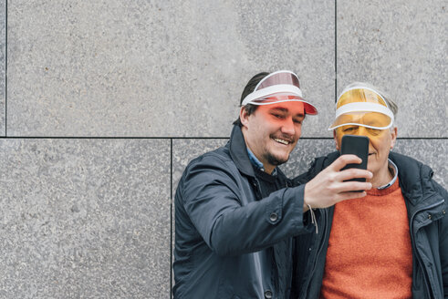 Smiling young man and senior man wearing sun visors taking a selfie - GUSF00653