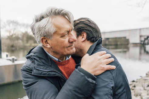 Young man and senior man embracing at the riverside - GUSF00659