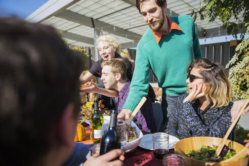 Man serving food to friends during garden party - CAVF48235