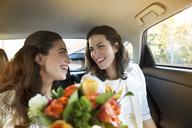 Happy lesbian wedding couple in car - CAVF48250