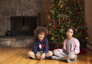 Portrait of siblings sitting against Christmas tree at home - CAVF48277