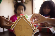 Family decorating gingerbread house at home - CAVF48292