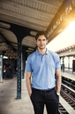 Portrait of man with hands in pockets standing at railroad platform - CAVF48466