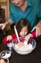 Woman assisting granddaughter for preparing food at home - CAVF48601