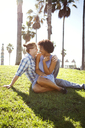 Smiling couple sitting on grassy field - CAVF48694