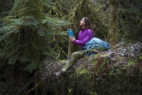 Woman holding bottle looking up while sitting on fallen tree trunk in forest - CAVF48754