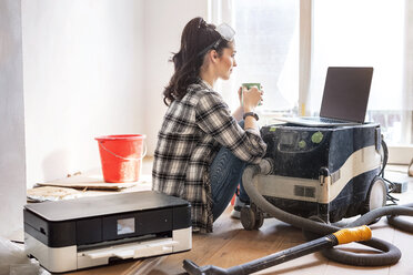 Young woman renovating her new flat, drinking coffee, looking at laptop - PESF01038