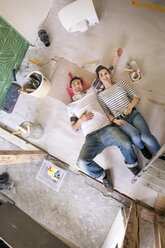 Happy couple renovating new home, taking a break, daydreaming - PESF01056