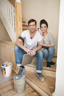 Young couple refurbishing new home, sitting on stairs using digital tablet - PESF01062