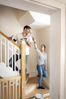 Young couple refurbishing new home, painting staircase - PESF01065