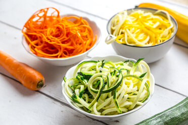 Zoodles, green and yellow zucchini, carrot on white wood - SARF03674