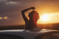 Woman outside the car at sunset, raised arm - JPF00304