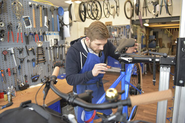 Bicycle mechanic working in his repair shop - LYF00810