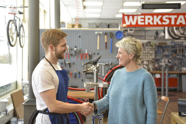 Salesperson helping customer in bicycle shop - LYF00831