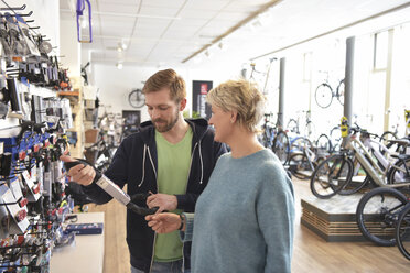 Salesperson helping customer in bicycle shop - LYF00834
