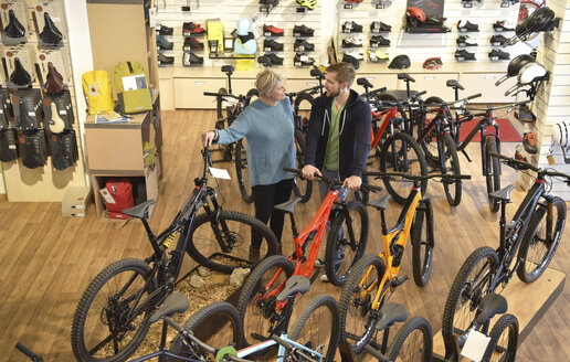 Salesperson helping customer in bicycle shop - LYF00837