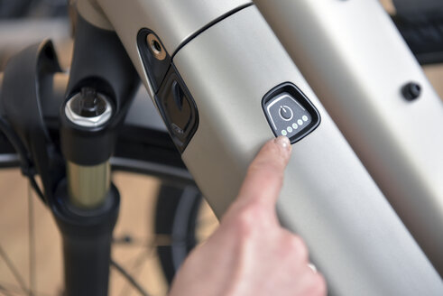 Finger pointing on switch of an e-bike - LYF00840