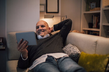 Senior man lying on couch, reading e-book - GUSF00675