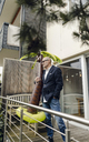 Senior businessman standing in his garden, holding a rubber palm, dreaming of vacations - GUSF00714
