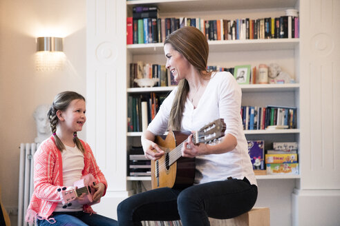 Mother and daughter playing guitar together at home - MOEF01081