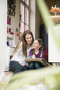 Mother and daughter painting together at home - MOEF01093
